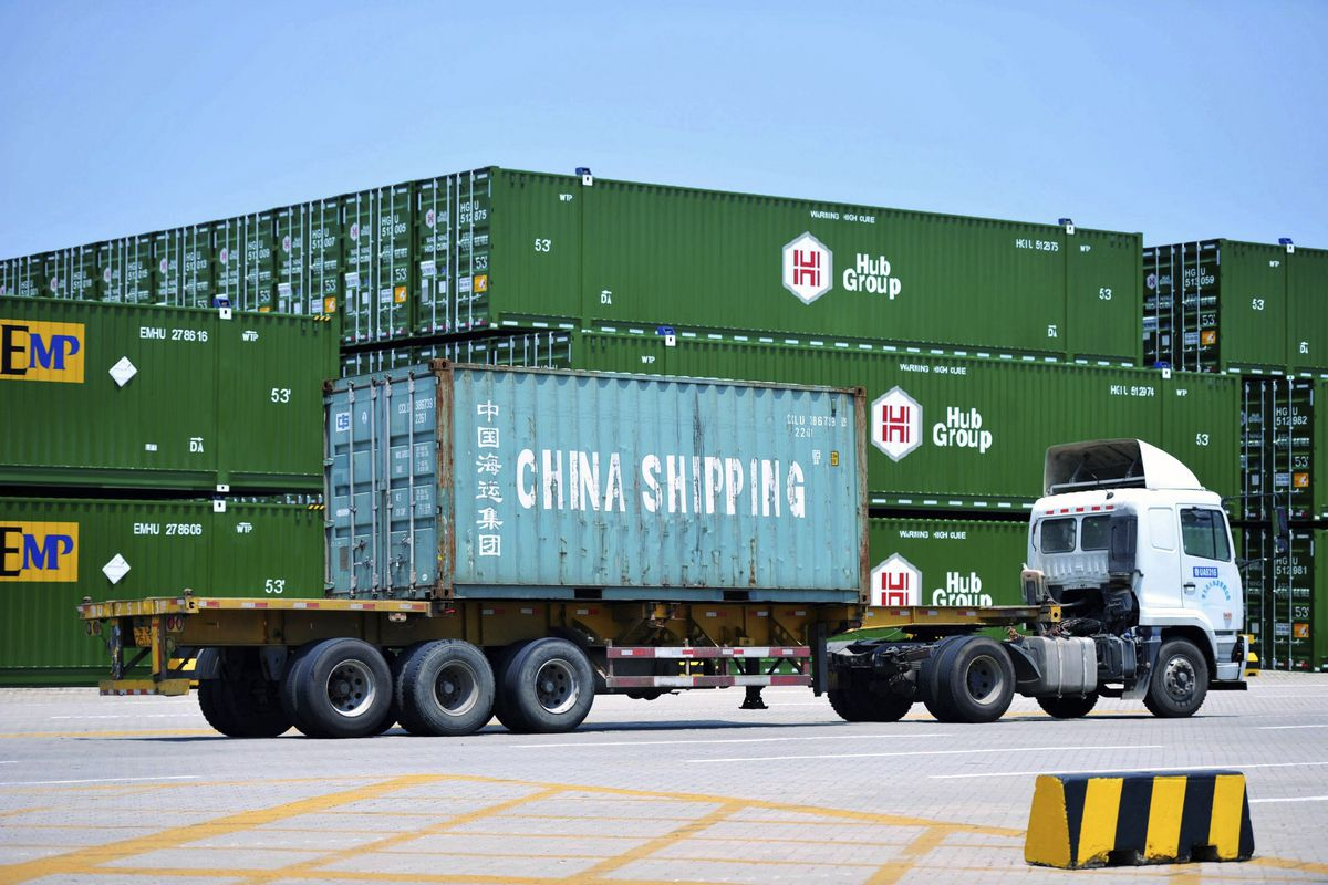 In this July 6, 2018, photo, a truck moves a China Shipping shipping container at a port in Qingdao in eastern China's Shandong Province.