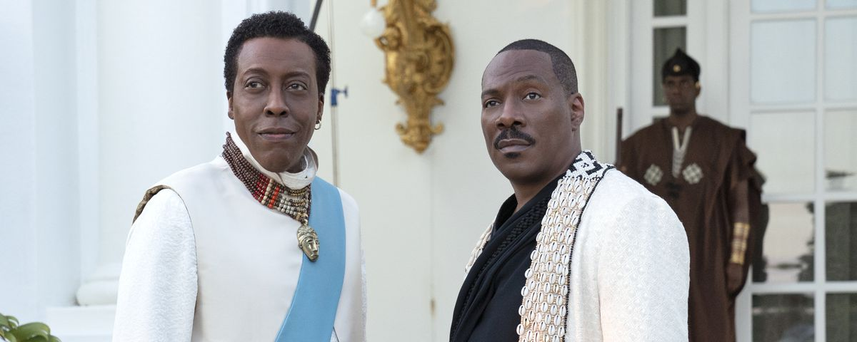 Arsenio Hall and Eddie Murphy, dressed in formal white outfits, stand outdoors in Coming 2 America