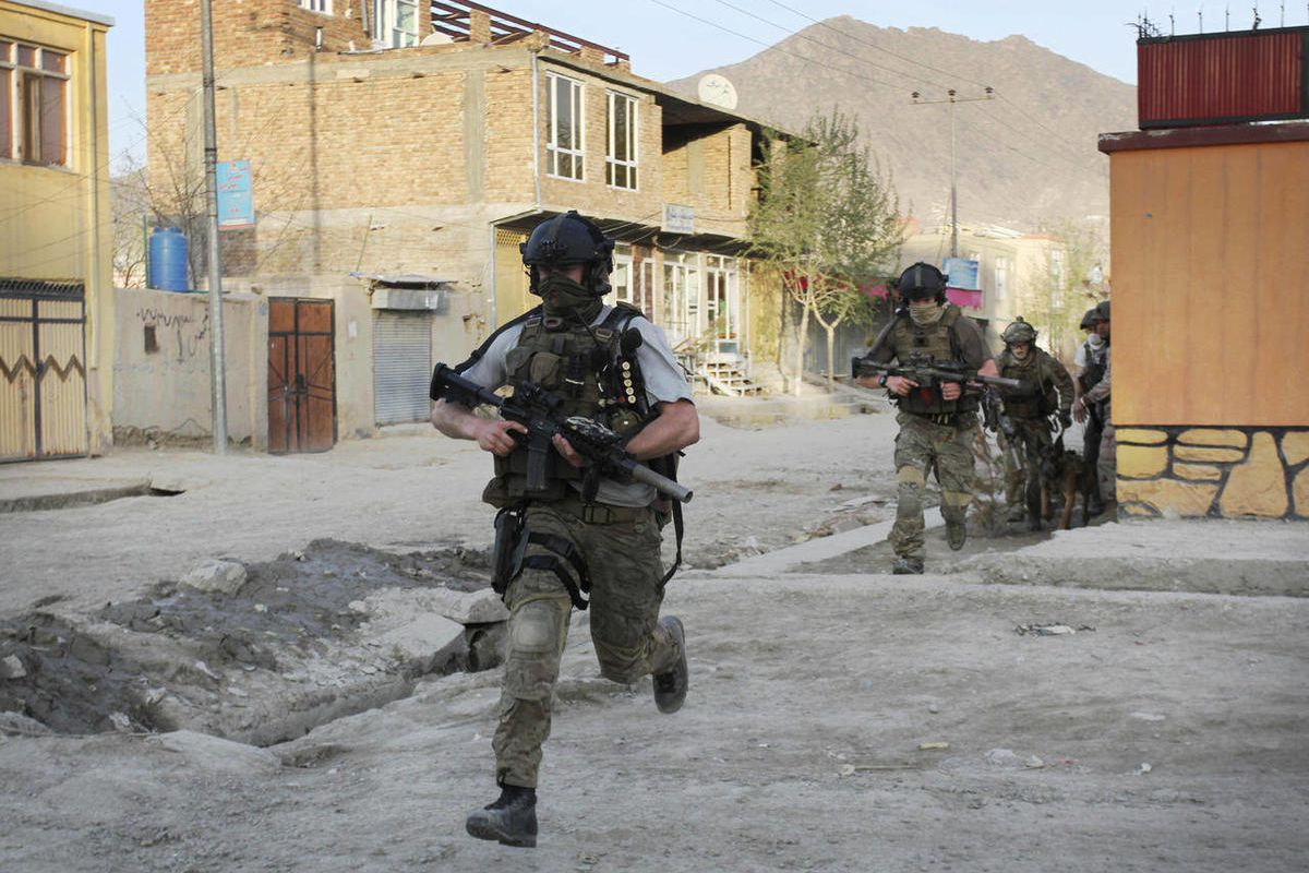 FILE  -- In an April 15, 2012 file photo NATO soldiers run during a gun battle in Kabul, Afghanistan. The United States and its NATO allies are readying plans to pull away from the front lines in Afghanistan next year as President Barack Obama and fellow