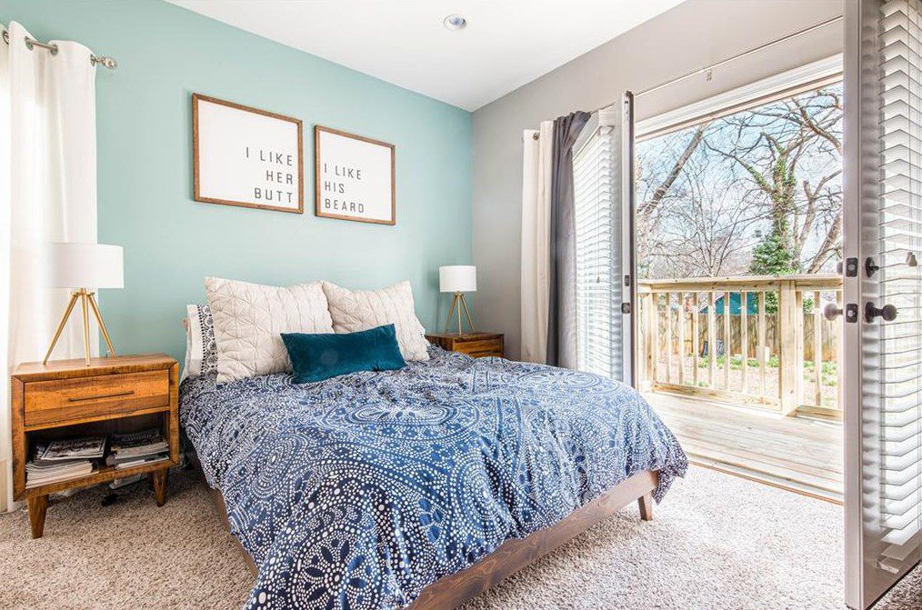 A blue master bedroom with gray carpeting and french doors.