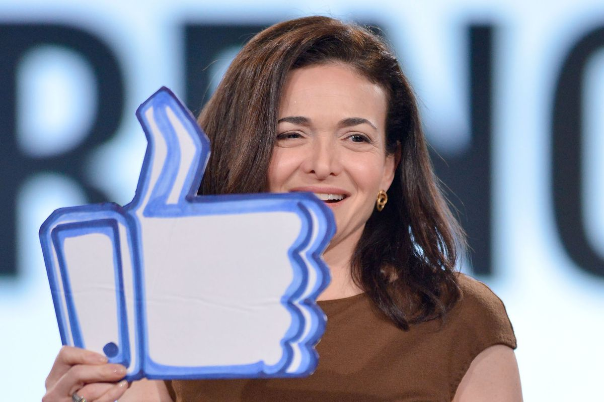 Facebook COO Sheryl Sandberg holding up a cardboard cutout of a thumbs-up symbol