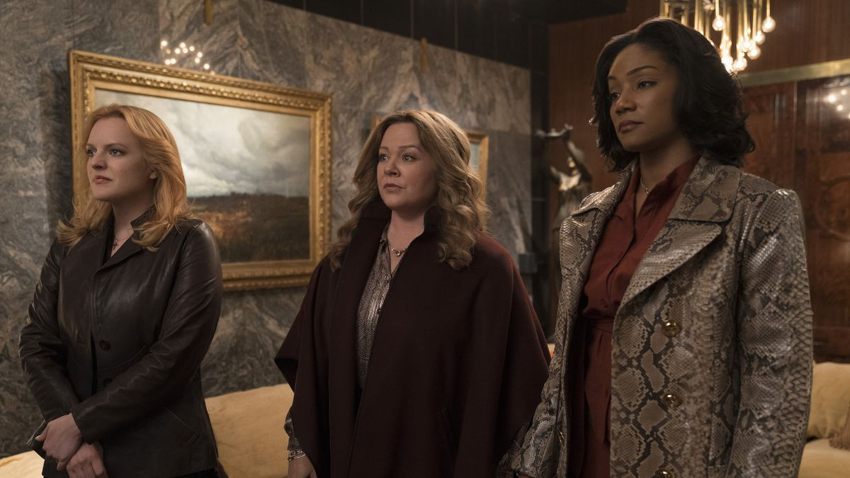 Looking somber, Claire (Elisabeth Moss), Kathy (Melissa McCarthy), and Ruby (Tiffany Haddish) wait in a gaudily decorated room in The Kitchen
