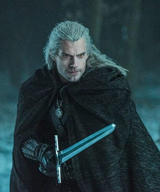 geralt bends his knees and holds a sword while covered in a cloak