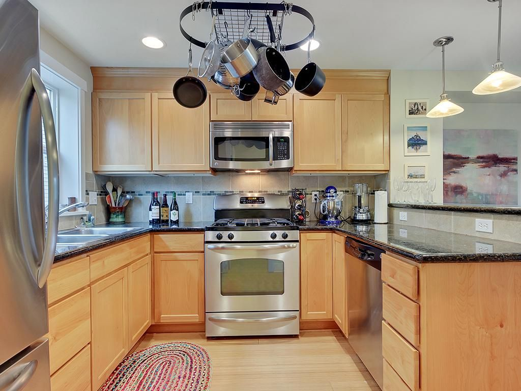 A kitchen in an open floorplan with dark gray counters, wood cabinets, and pots hanging above