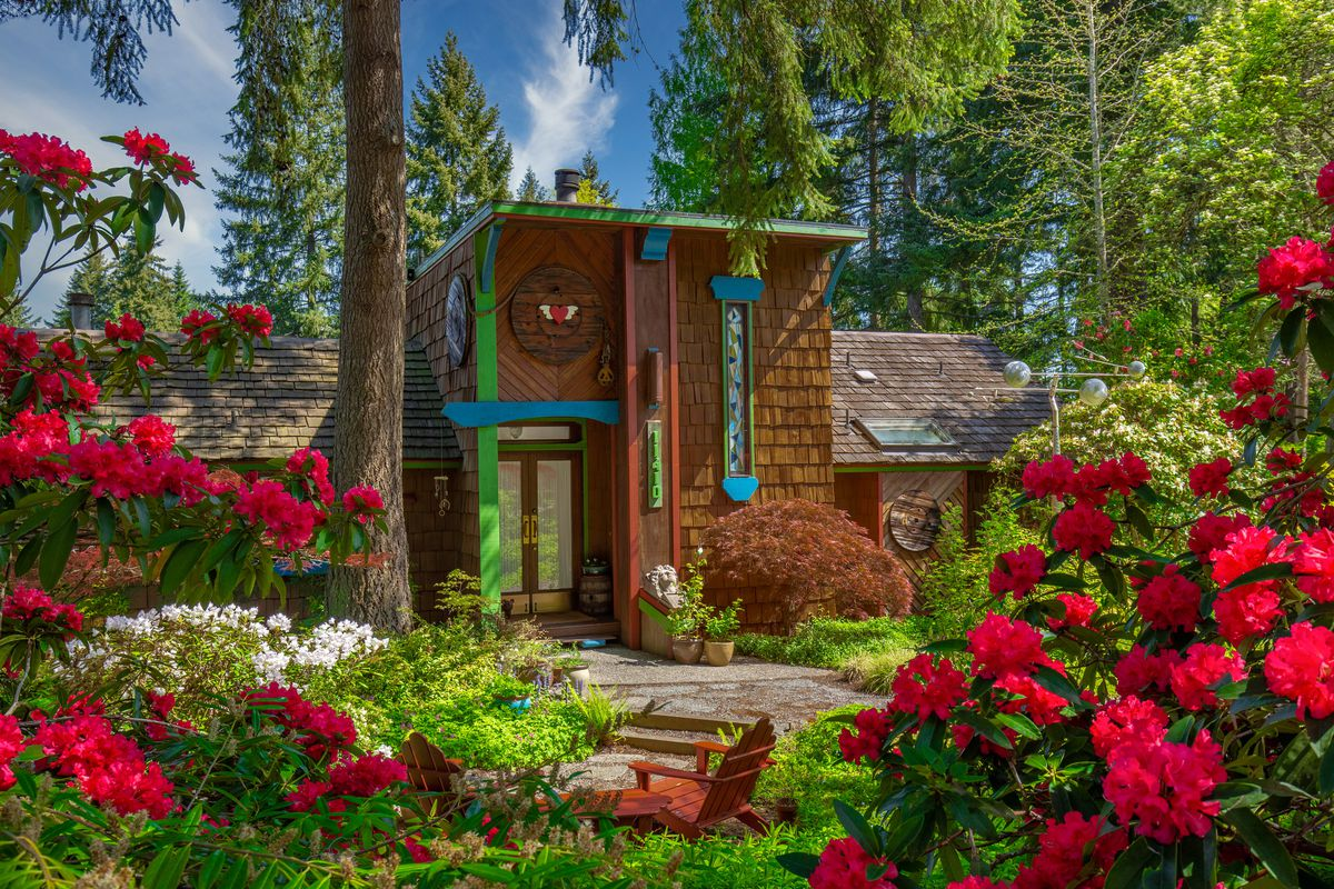 A brown cedar shake house with green and blue trim sits in a forested lot. There are red flowers in the foreground of the photo.