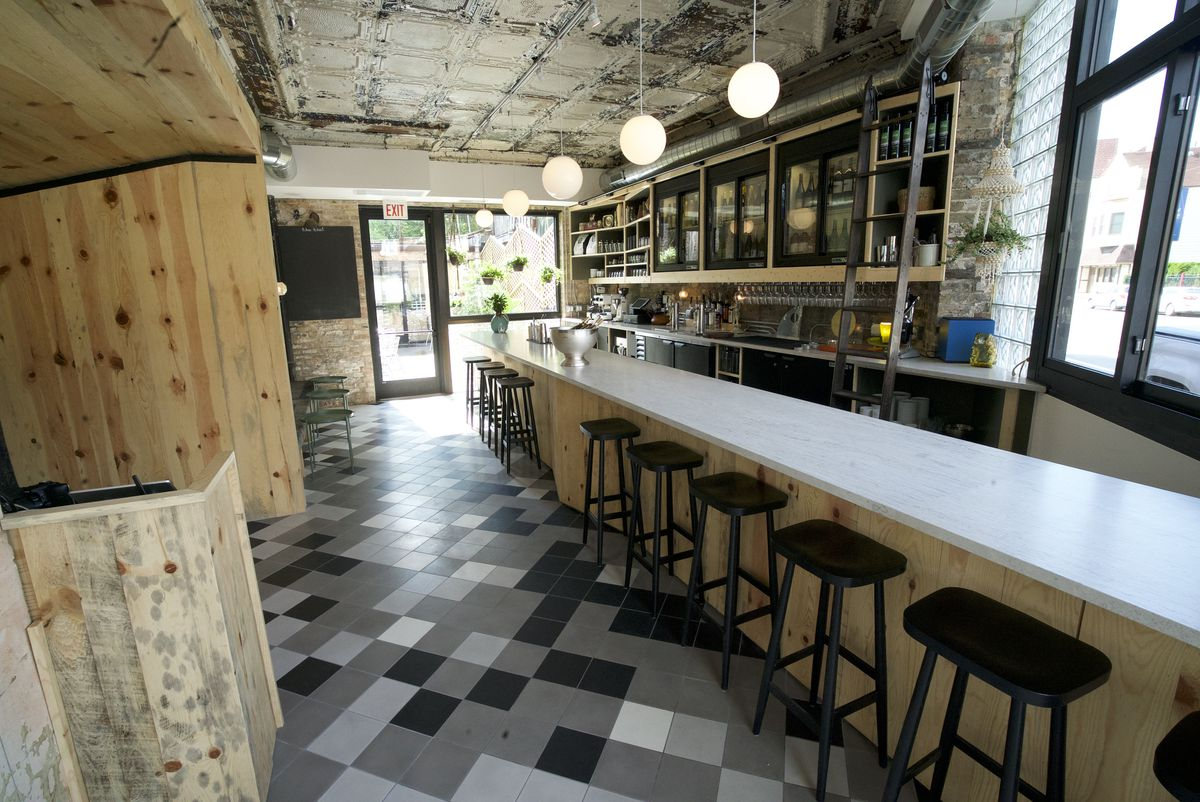 A bar's interior with black and white tiled floors.