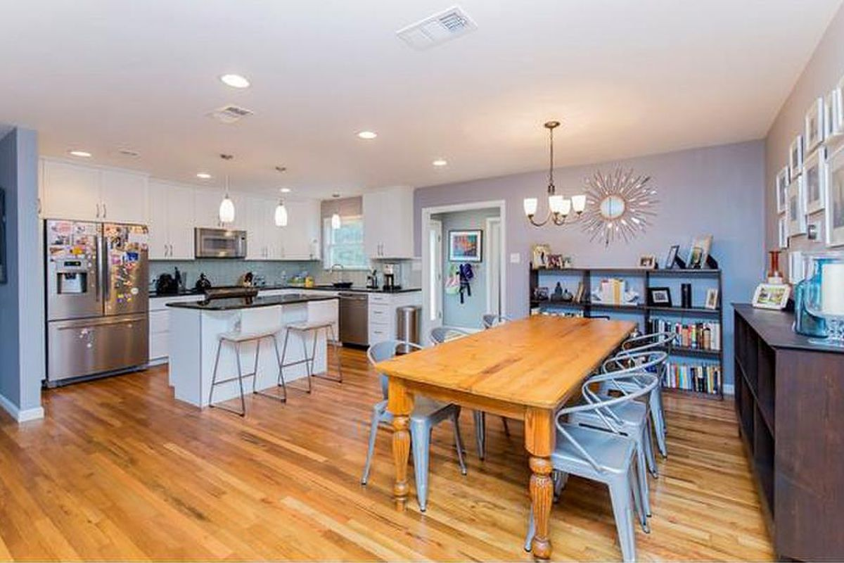 A large open-plan kitchen and dining space with contemporary but mostly traditional furnishings and lots of light blue accents
