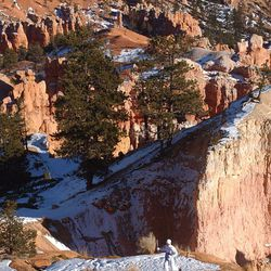 Bryce Canyon National Park ranger Steve Mazur carries the Olympic torch while running on snowshoes from Sunrise Point to Queens Garden and back again on Monday, Feb. 4, 2002.