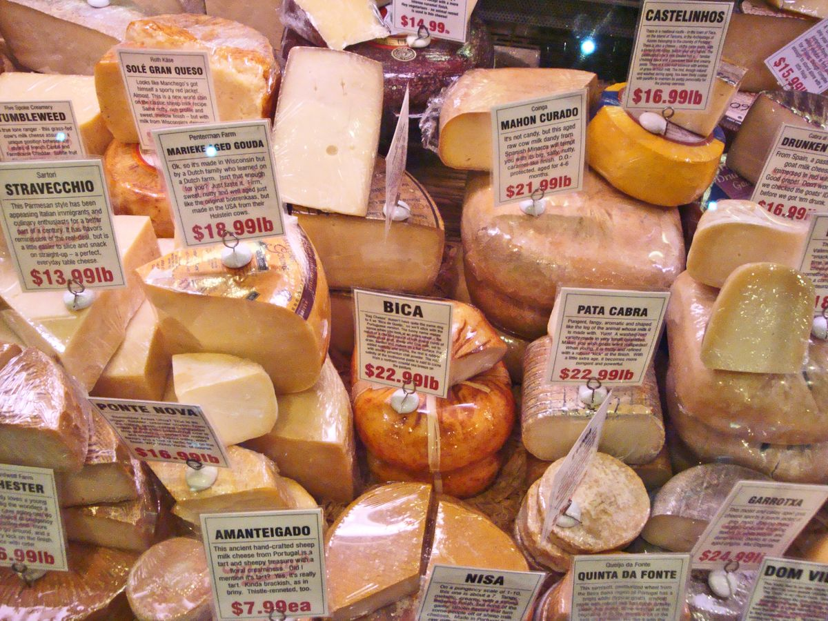 An open top cheese cooler filled with wedges, each with a sign naming and explaining it.