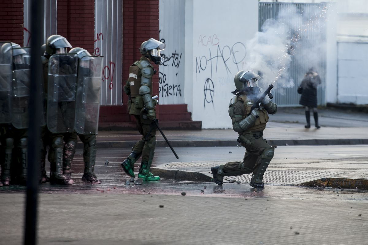 A police officer in riot gear shoots a tear gas canister while other officers hold up their shields.