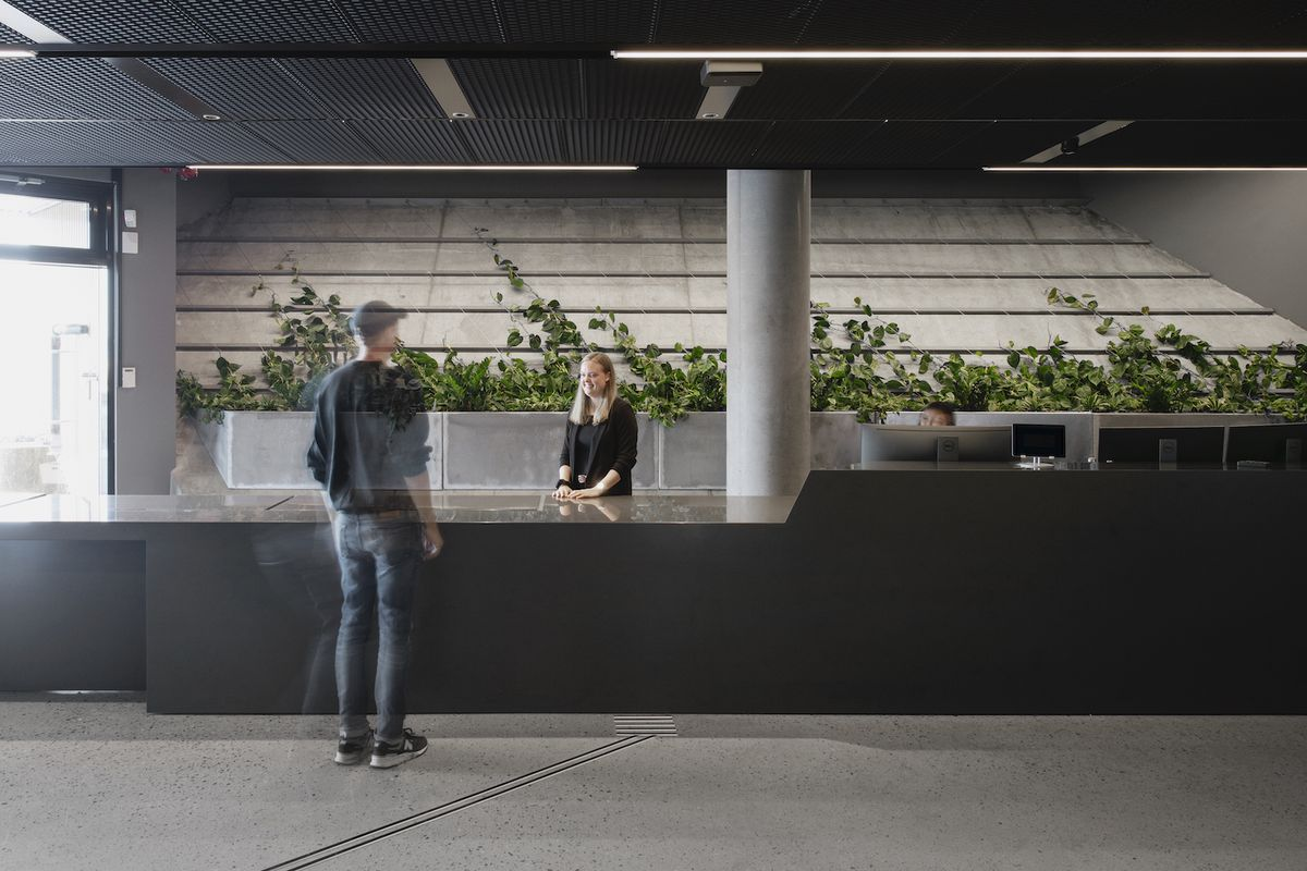 Man checking in at reception desk, which features black counters, a gray column, and plants alongside the back wall. A woman with blonde hair is working at the desk.
