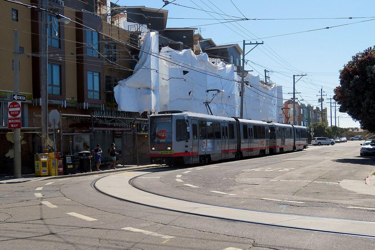 An L Taraval train passing some low-rise buildings.