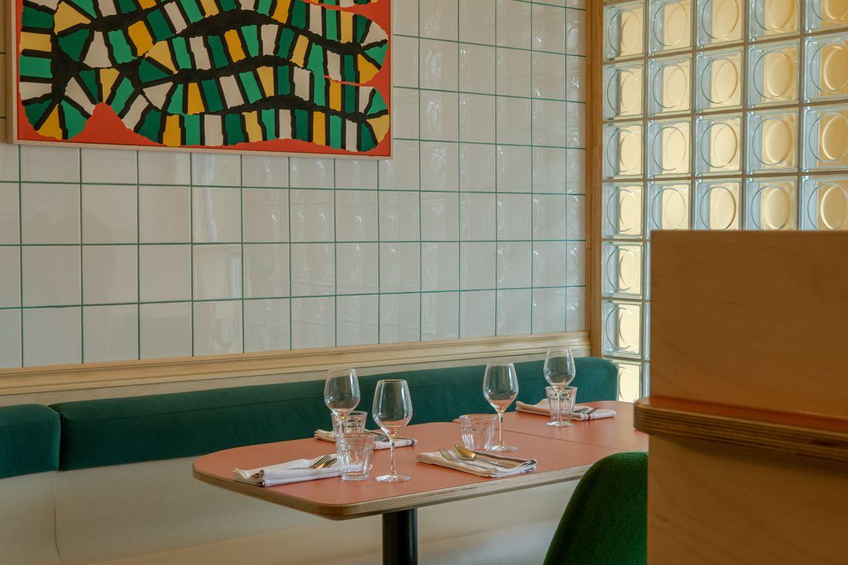 inside of restaurant with white tiles, peach tabletops