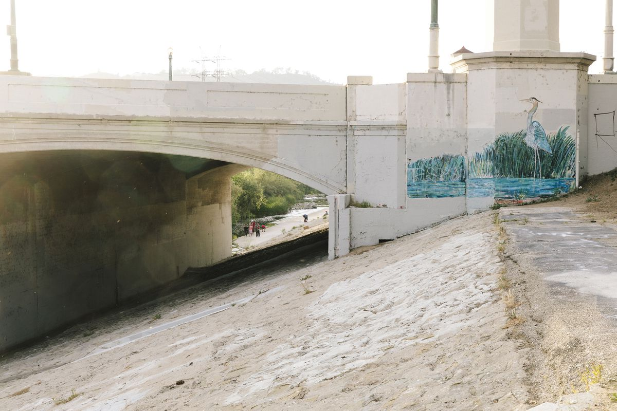 A concrete bridge with a concrete ledge and path below leading to a river and trees. A painting on the side of the bridge of a bird in the river.