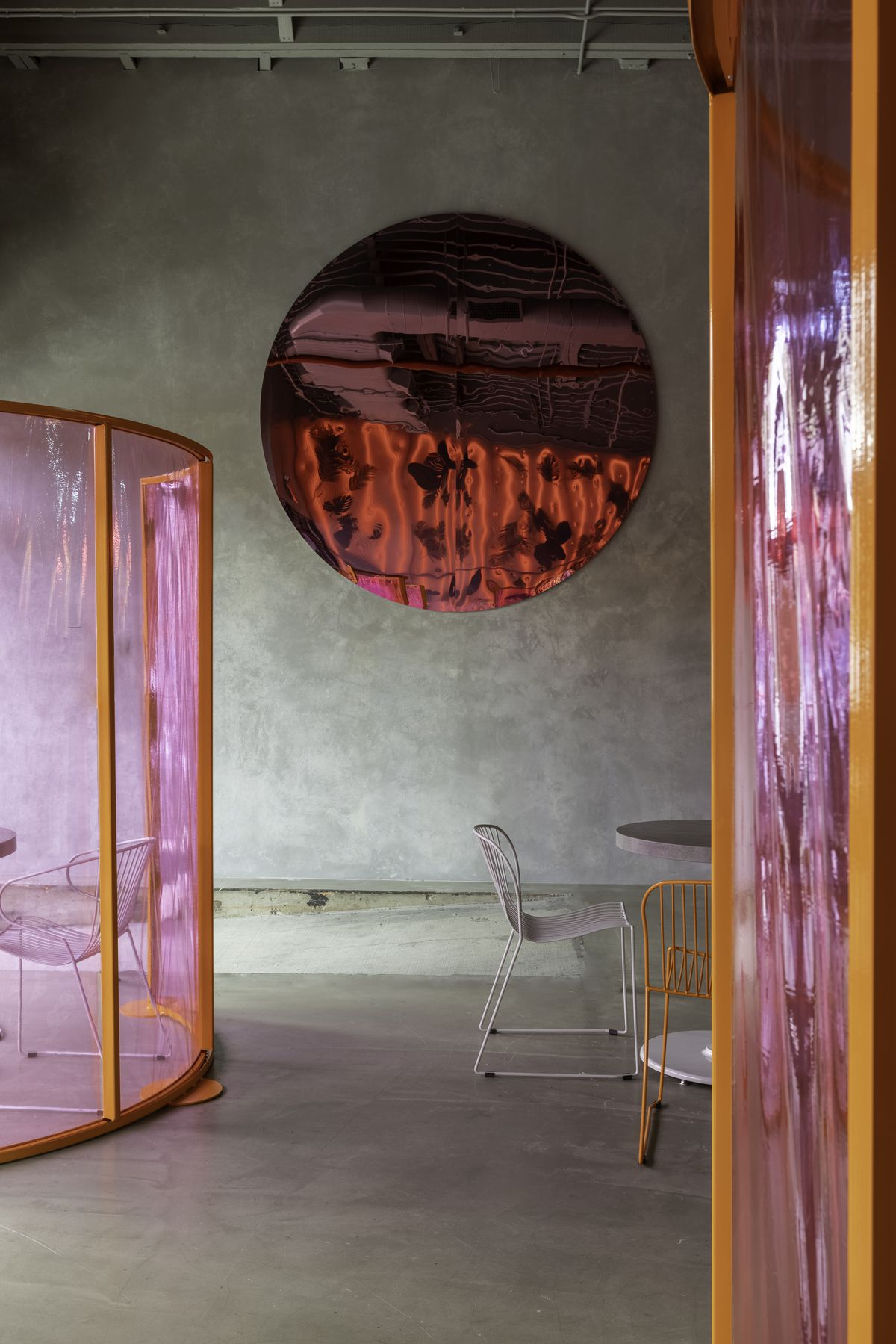 Colorful orange and pink dividers separate tables and chairs in the taproom at Wandering Barman