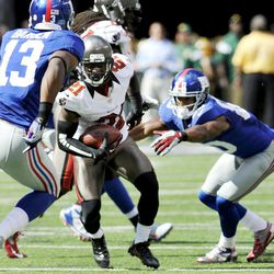Tampa Bay Buccaneers defensive back Eric Wright (21) breaks away from New York Giants wide receiver Victor Cruz (80) after intercepting a pass and running it back for a touchdown during the first half of an NFL football game, Sunday, Sept. 16, 2012, in East Rutherford, N.J.