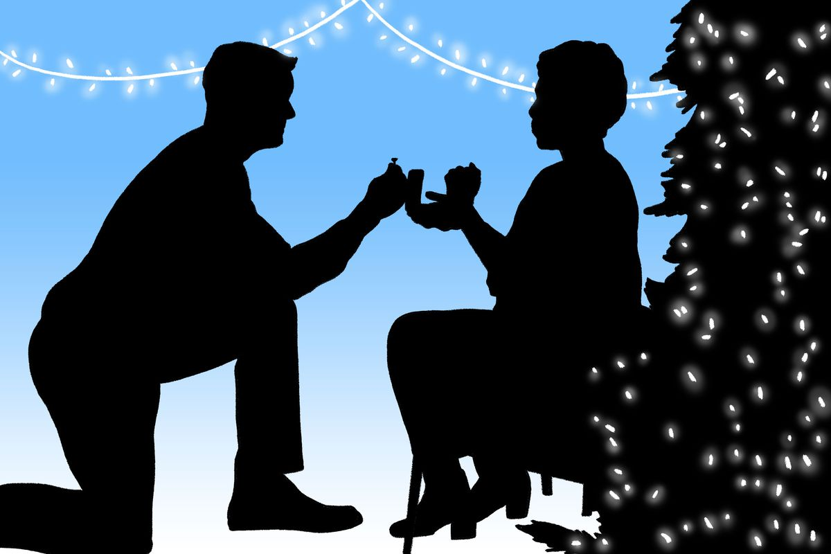 Silhouettes of a man proposing to a woman in front of a Christmas tree