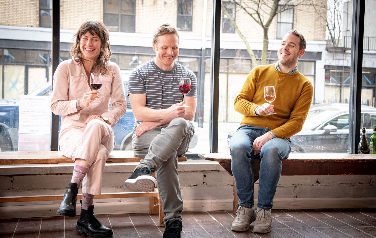 Three people are drinking wine, laughing, and sitting on a bench behind a glass window