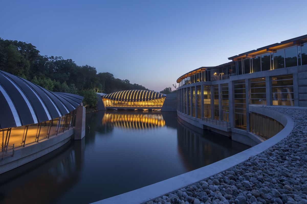 The exterior of the Crystal Bridges Museum of American Art in Arkansas. The building pavilions surround a pond.
