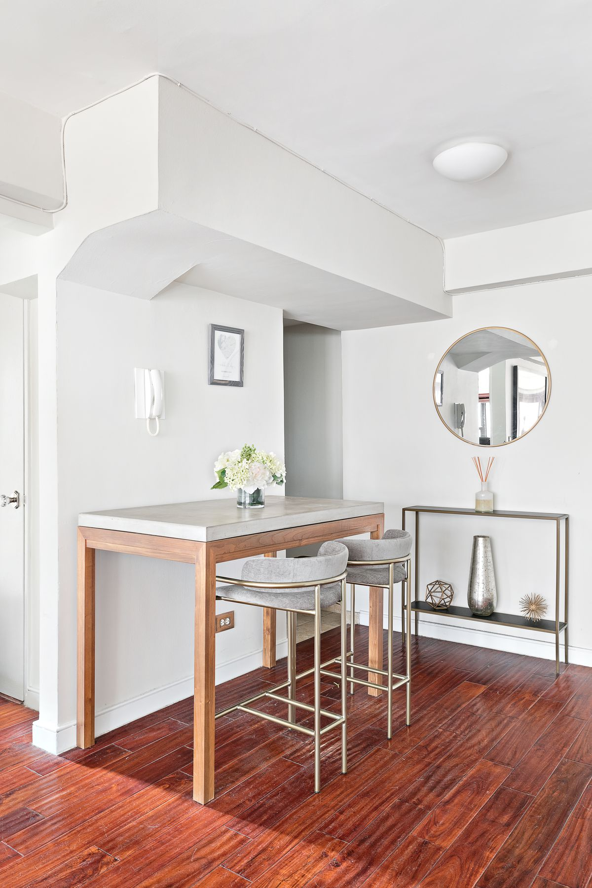 A dining nook with a table and two high top chairs.