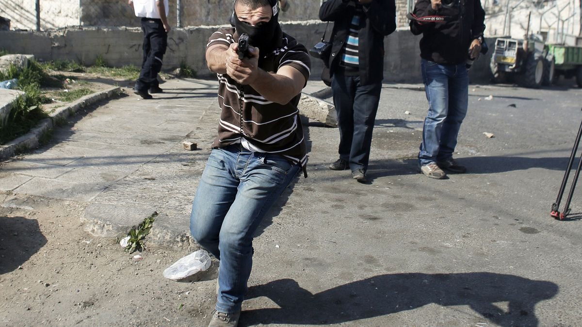 An Israeli policeman points his gun toward Palestinian demonstrators and photographers during clashes in East Jerusalem