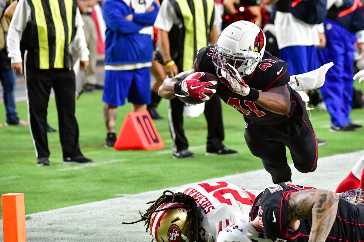 Arizona Cardinals running back Kenyan Drake dives over San Francisco 49ers cornerback Richard Sherman to score a touchdown in the first quarter at State Farm Stadium.
