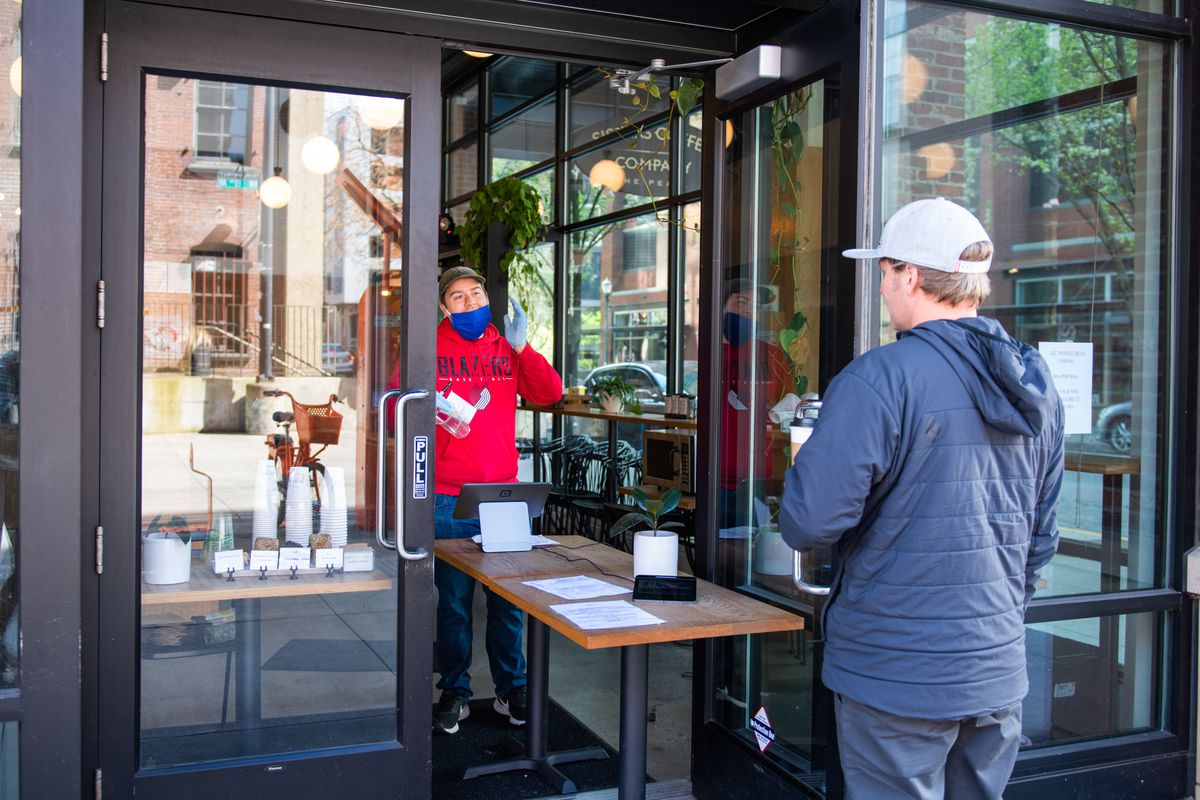The doors of the Sisters cafe in the Pearl District barely remain open, with a long wooden table jutting out on either side of the doors. A man wearing a blue mask and gloves speaks to a customer on either end of the long wooden table.