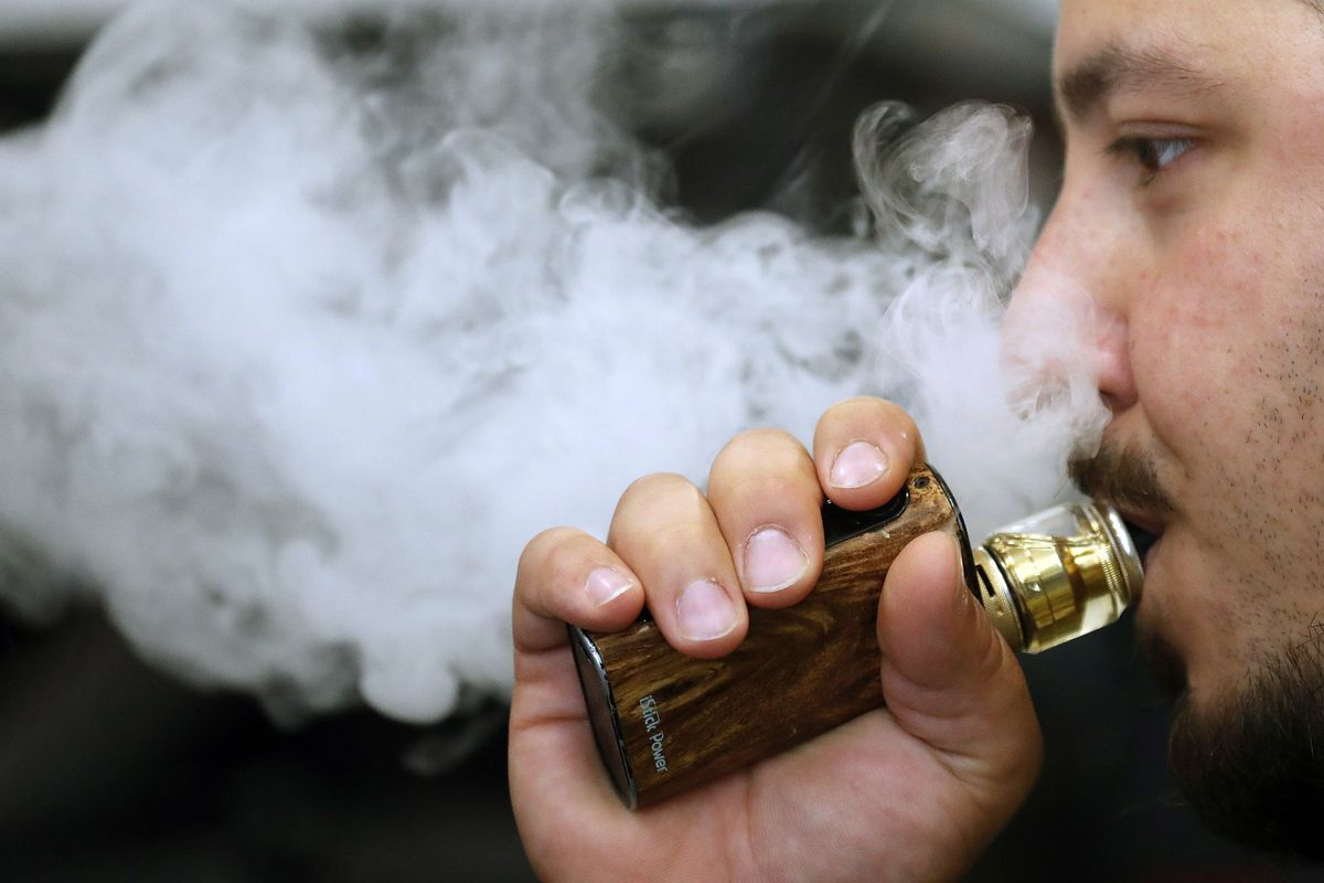 A man breathes vape from an e-cigarette at a vape shop in London, Friday, Aug. 17, 2018.