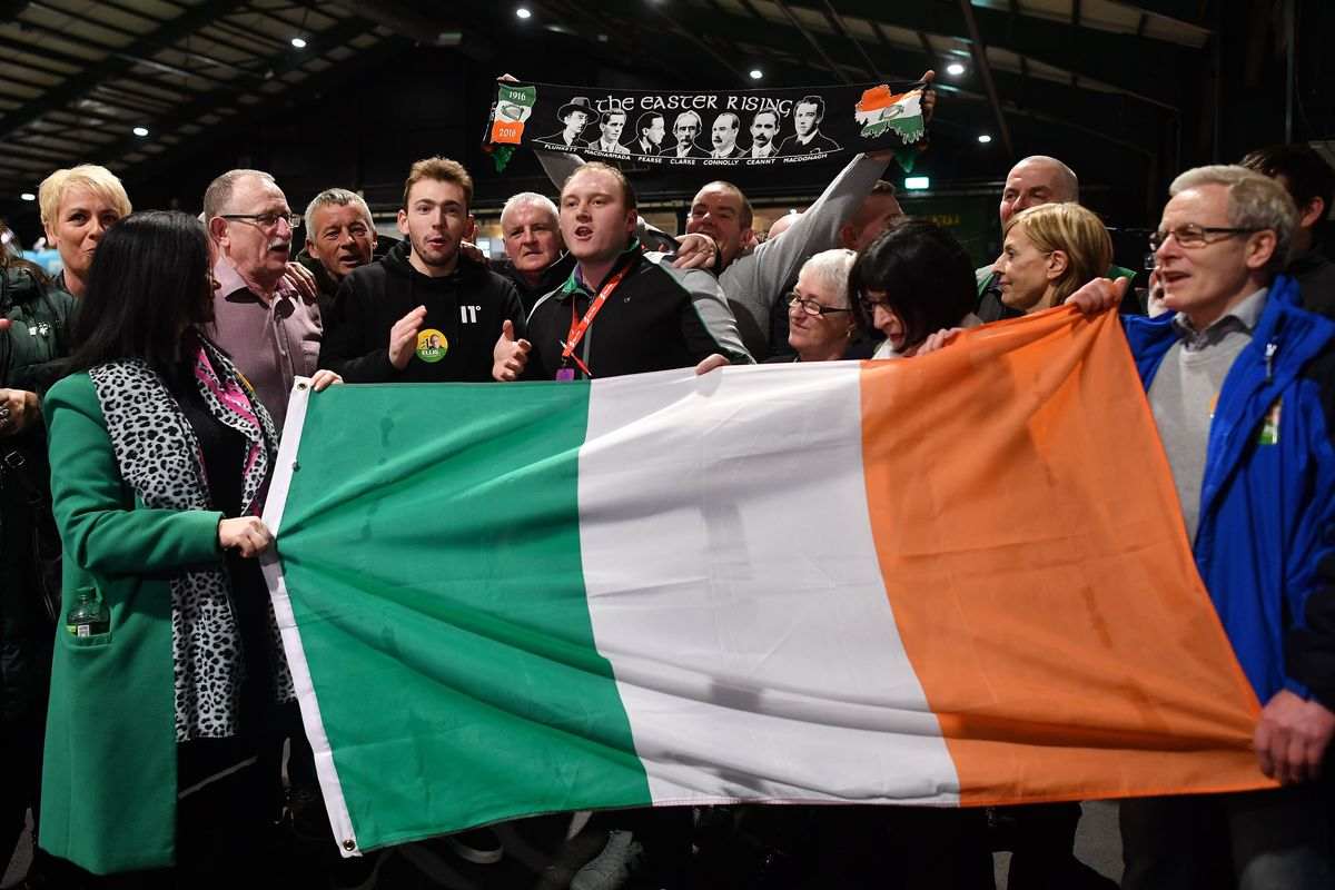 Post-election celebration in Ireland where several people hold an Irish flag.