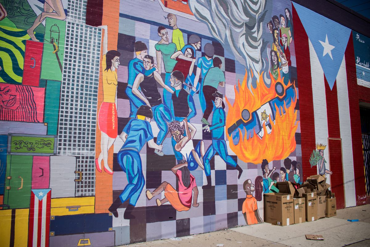 """Cristian Roldán painted this large mural, titled """"Repression, Resistance and Resilience,"""" in 2016. It chronicles the history of Puerto Rico and the migration of people from the island to Chicago, ending with the 1966 Division Street riots."""
