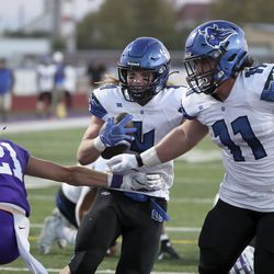 Pleasant Grove's Rex Connors scores a touchdown between Lehi's Kadiyon Sweat and Pleasant Grove's Spencer Tauteoli during a football game at Lehi High School in Lehi on Friday, Sept. 11, 2020.
