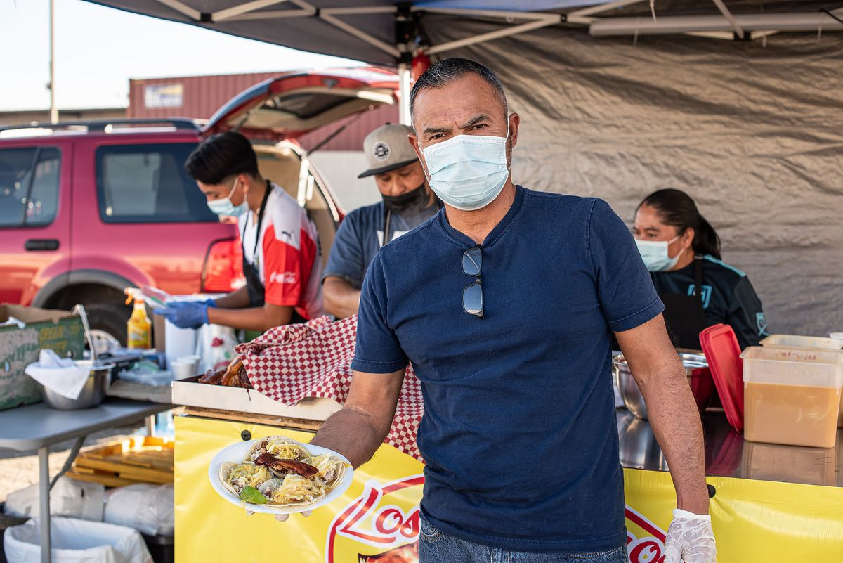 A taco stand owner holds a plate of tacos from behind a mask.