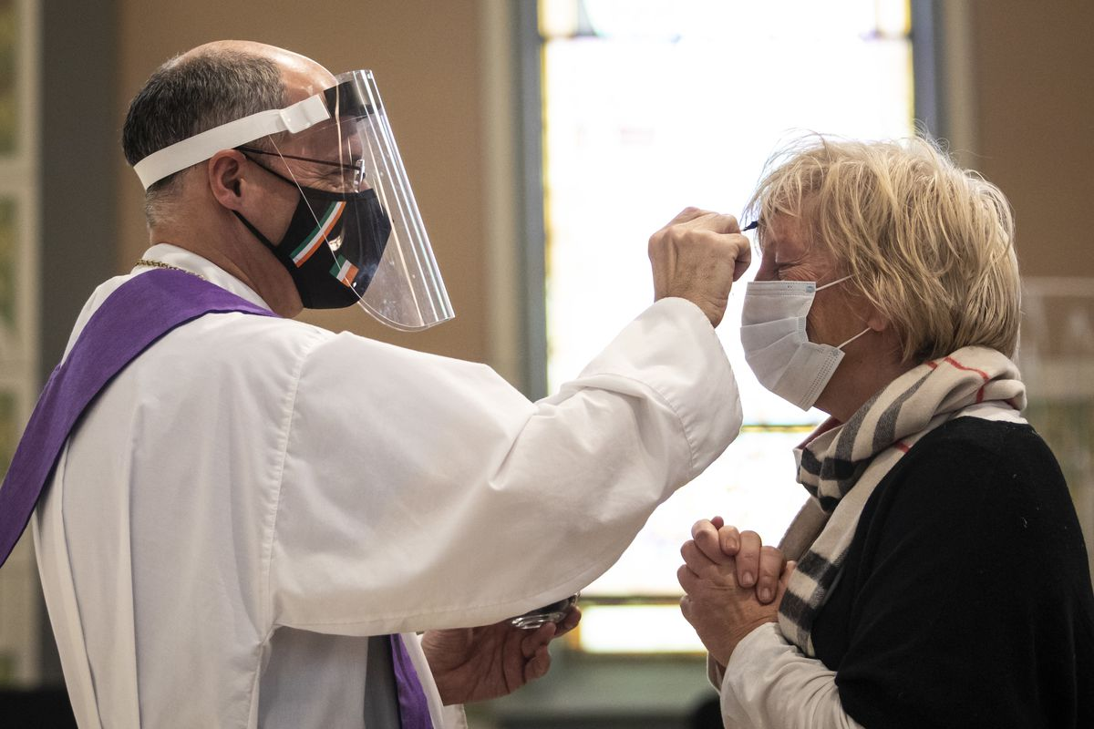 Lori Hiltz, 60, of Streeterville, receives the imposition of ashes from Rev. Tom Hurley at Old St. Patrick's Catholic Church on the Near West Side on Ash Wednesday. Amid fears of the coronavirus pandemic, Hurley did not touch anyone and gave out ashes on a fresh Q-tip to each parishioner, then threw the Q-tip away.