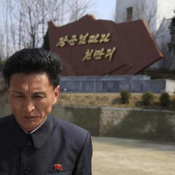 A North Korean man stands near a monument calling for the people to follow Kim Jong Il's leadership outside North Korea's space agency's General Launch Command Center in Pyongyang, North Korea, Wednesday, April 11, 2012. Engineers are pumping fuel into a rocket that is set to carry a satellite into space, officials at the North Korean space agency's central command center said Wednesday, showing reporters a live feed of the west coast launch pad.