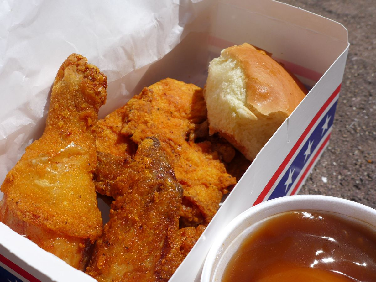 A carryout box of fried chicken and a not very good looking biscuit in a carryout box with a red white and blue motif...