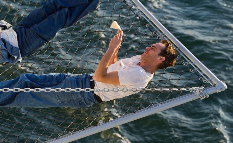 A man lies in a net, suspended above water.