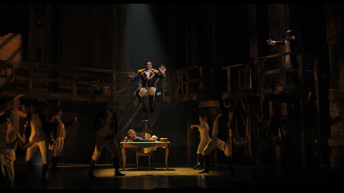 Daveed Diggs jumps at the center of the stage in Hamilton.