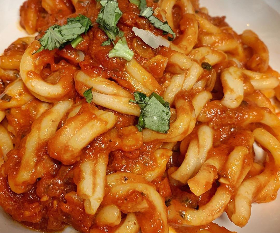A white plate of a short, twisty pasta in a tomato sauce, garnished with torn basil
