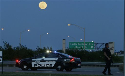 <small><strong>An armed police officer stands guard on a road near the Curtis Culwell Center in Garland, Texas.   LM Otero/AP</strong></small>