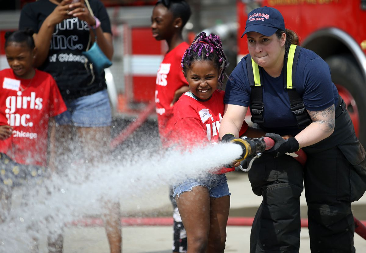 Chicago firefighter Jasmine Trace teaches Sophia to use a fire hose Friday June 28, 2019.