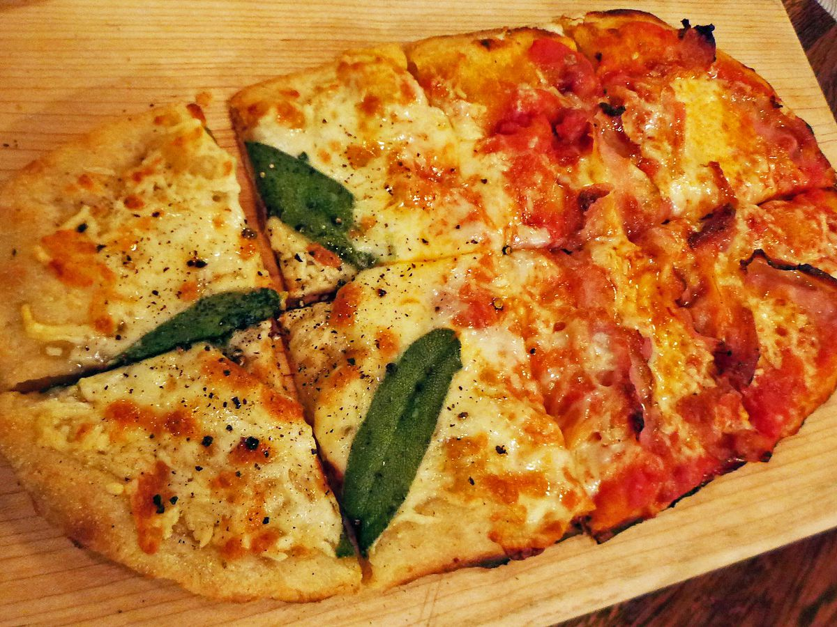 The Roman pizza called pinsa, a thick oblong of dough with two sauces.