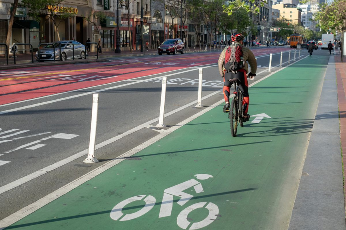 A lone cyclist in the middle of a green protected bike lane on Market Street.