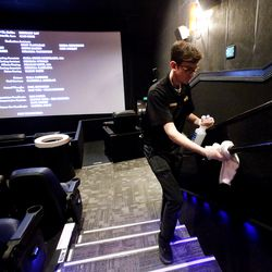 Jordan Atwood clean a handrail between movies at the Megaplex Theatres at Jordan Commons in Sandy on Friday, March 13, 2020.