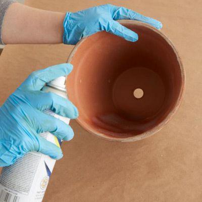 Person Sprays Inside Of Terracotta Pot With Matte Sealer