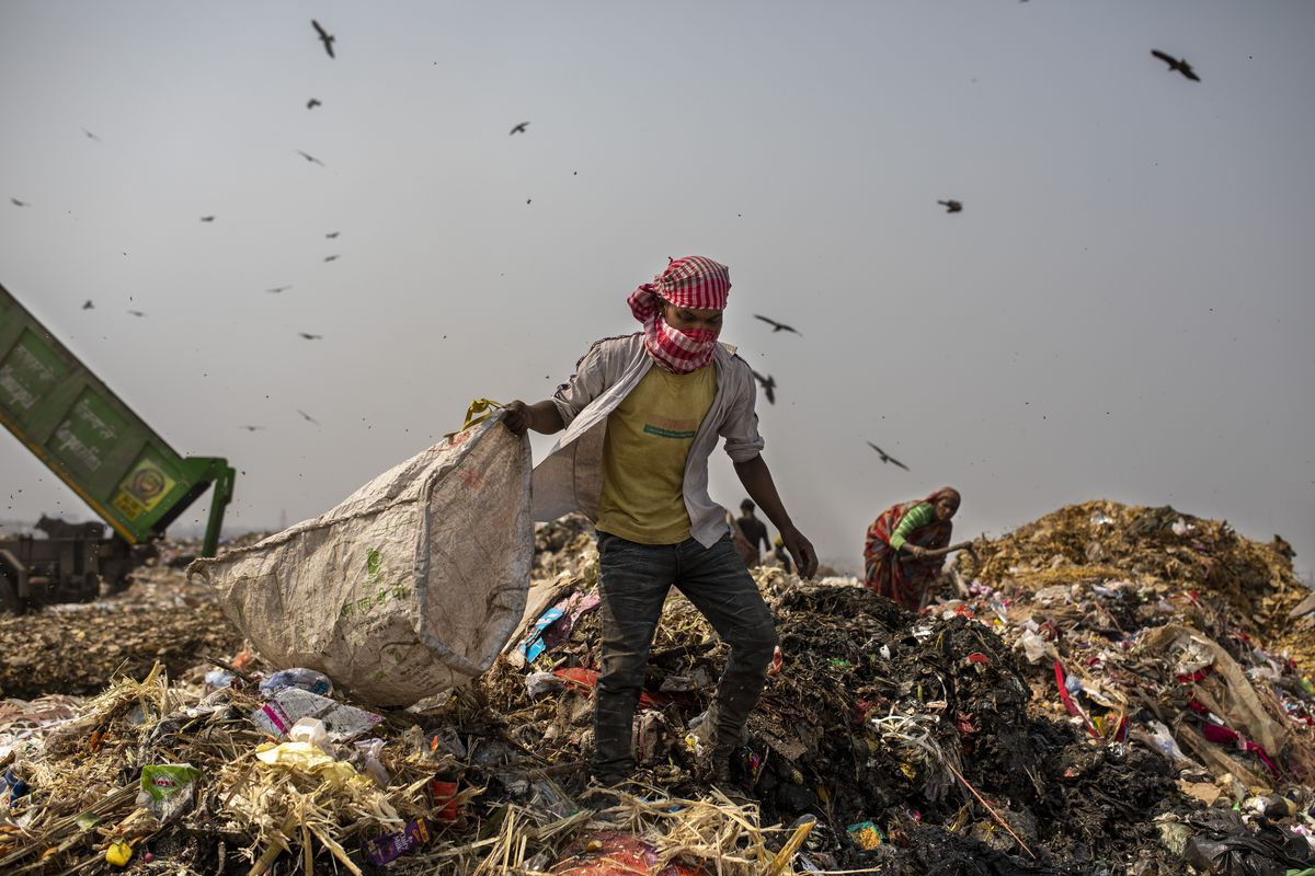 Trash workers look for recyclables at Bhalswa landfill on the outskirts of New Delhi, India, Wednesday, March 10, 2021.