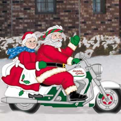 A wooden Christmas yard decoration featuring Mr. Claus driving a motorbike with Ms. Claus behind him.
