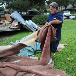 Mitch Smith pulls wet carpet from his home in LaPlace, La., Friday Aug. 31, 2012 that was flooded by Hurricane Isaac. Residents across the area began the long process of cleaning up after flooding caused by Hurricane Isaac.