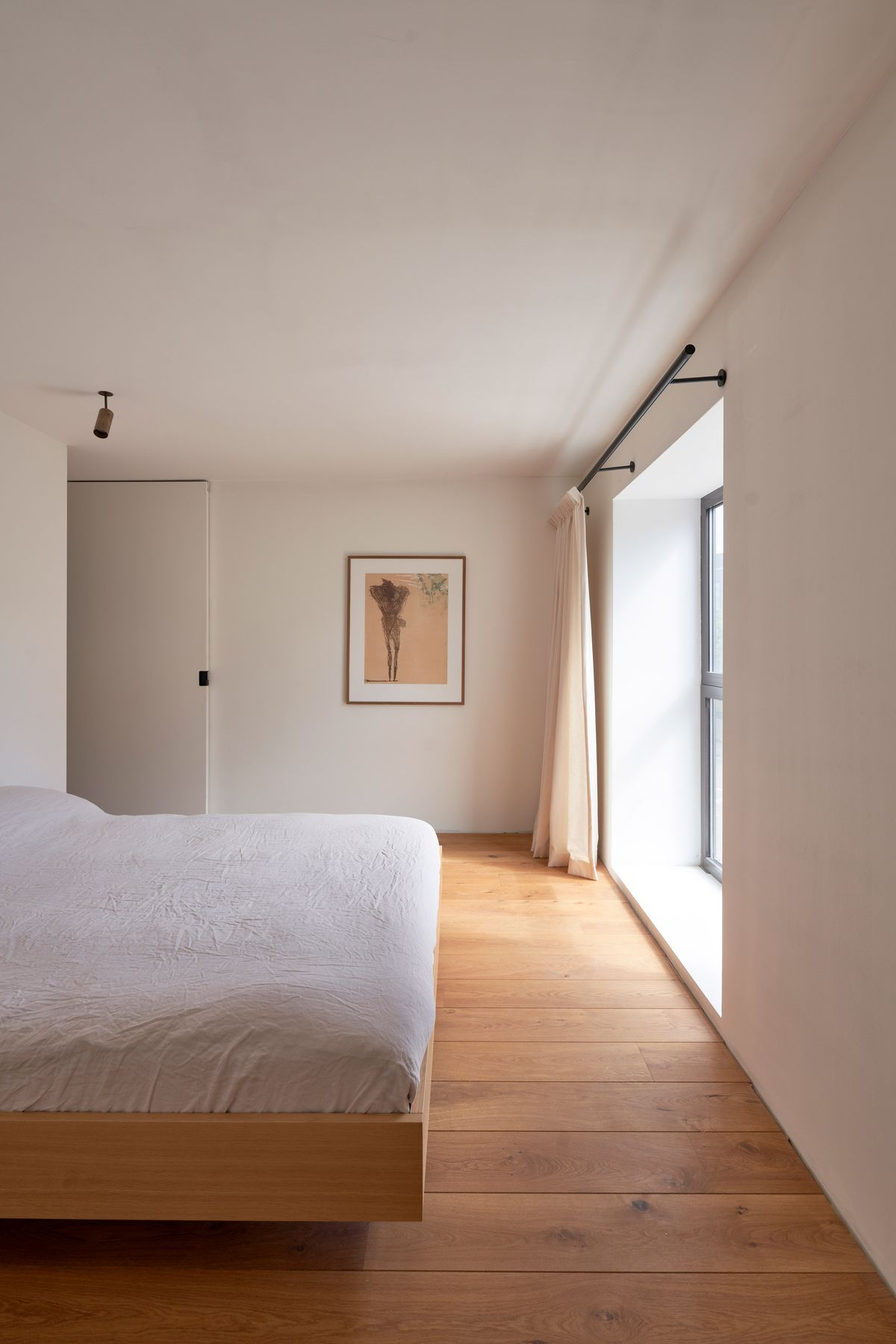 Bedroom with wood floors and white walls