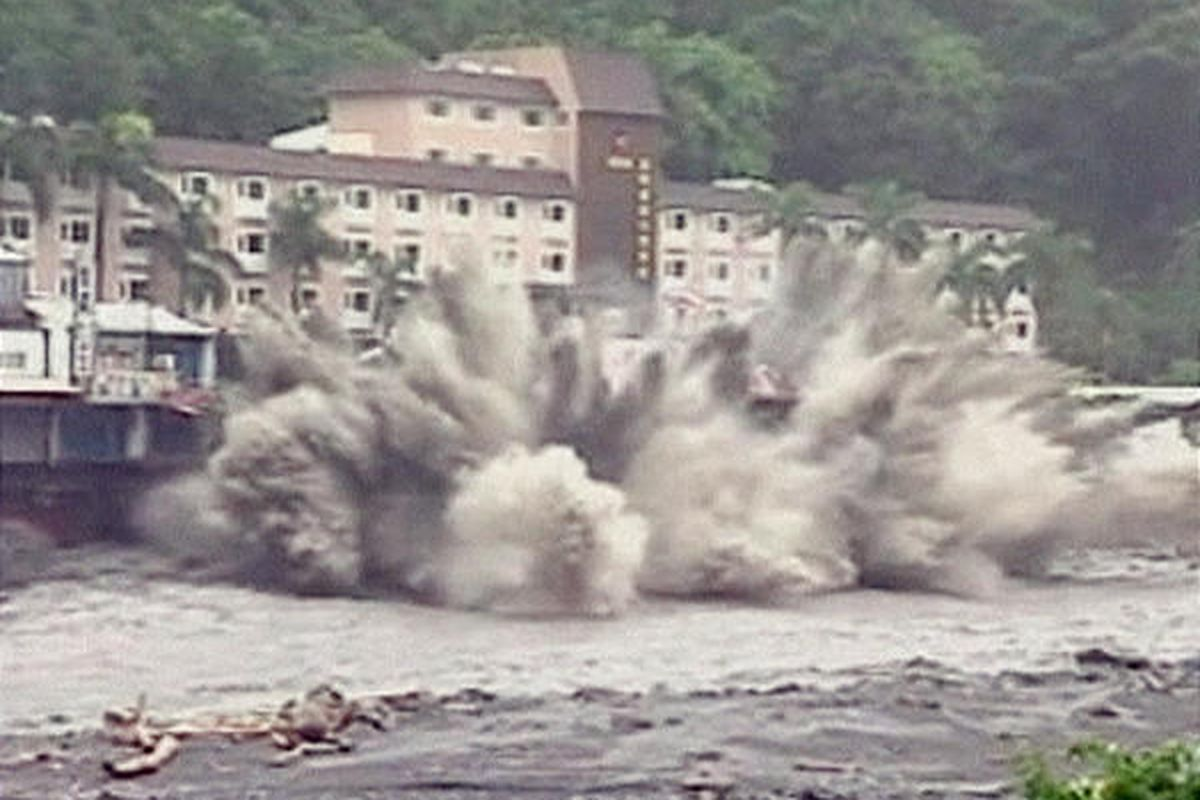 In this image from television, a six-story hotel in Chihpen, Taiwan, collapses and plunges into a river after floodwaters eroded its base.