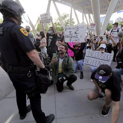 Protesters plead for police officers to join them and take a knee outside of the Salt Lake Public Safety Building in Salt Lake City on Monday, June 1, 2020. Only one officer took a knee, for just a minute.